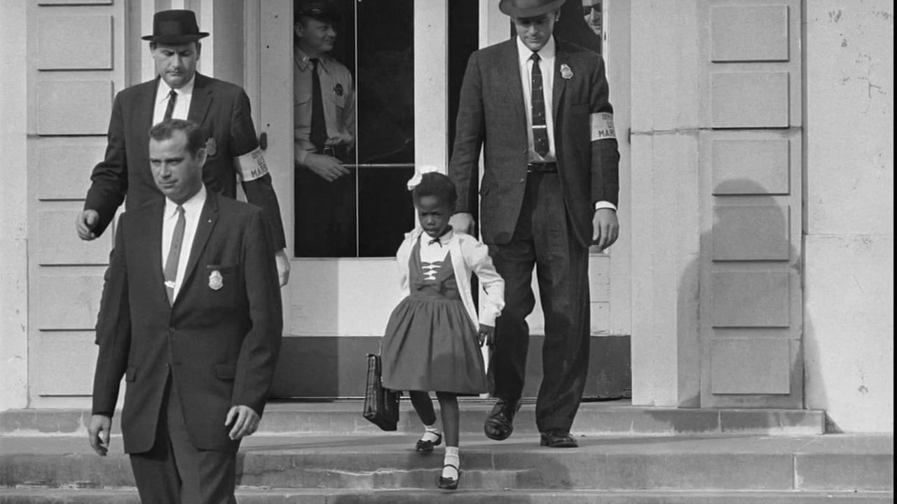 This undated image shows Ruby Bridges flanked by federal marshals as she walks out of a school in New Orleans.