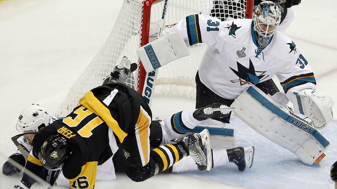 Penguins Eric Fehr hits the ice beside Sharks Martin Jones during Game 2 of the NHL hockey Stanley Cup Finals on June 1, 2016, in Pittsburgh. (AP Photo/Gene J. Puskar)