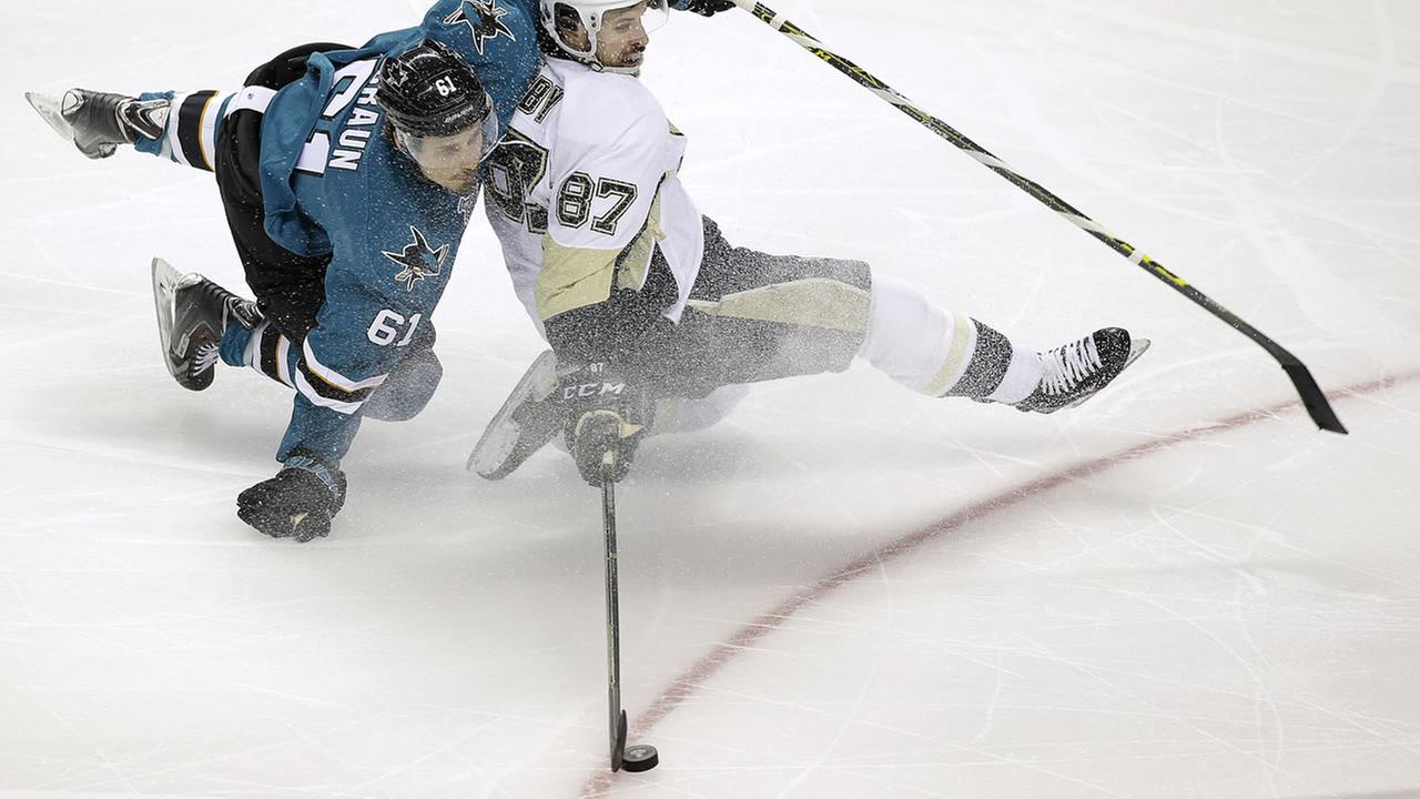 Pittsburgh Penguins center Sidney Crosby (87) reaches for the puck in front of San Jose Sharks defenseman Justin Braun (61) during Game 3  of the Stanley Cup Finals in San Jose.
