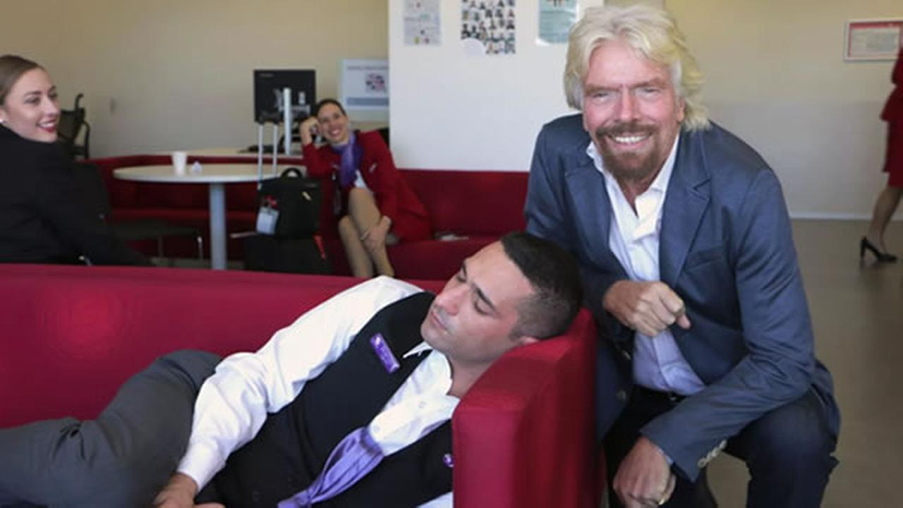 Virgin Airlines founder poses for a photo with a napping employee during a company visit in Australia.