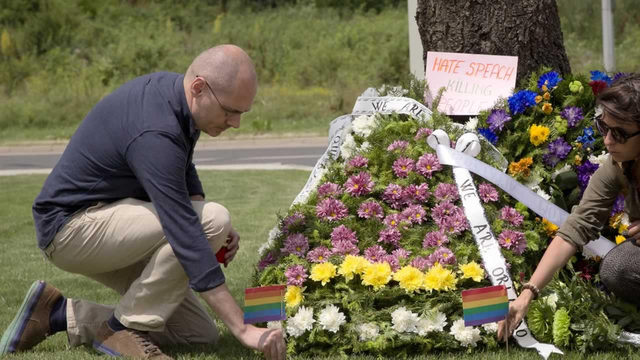 Florin Buhuceanu, left, leader of gay rights organization Accept, places a rainbow flag next to flower wreaths outside the US embassy in Bucharest, Romania, Tuesday, June 14, 2016.