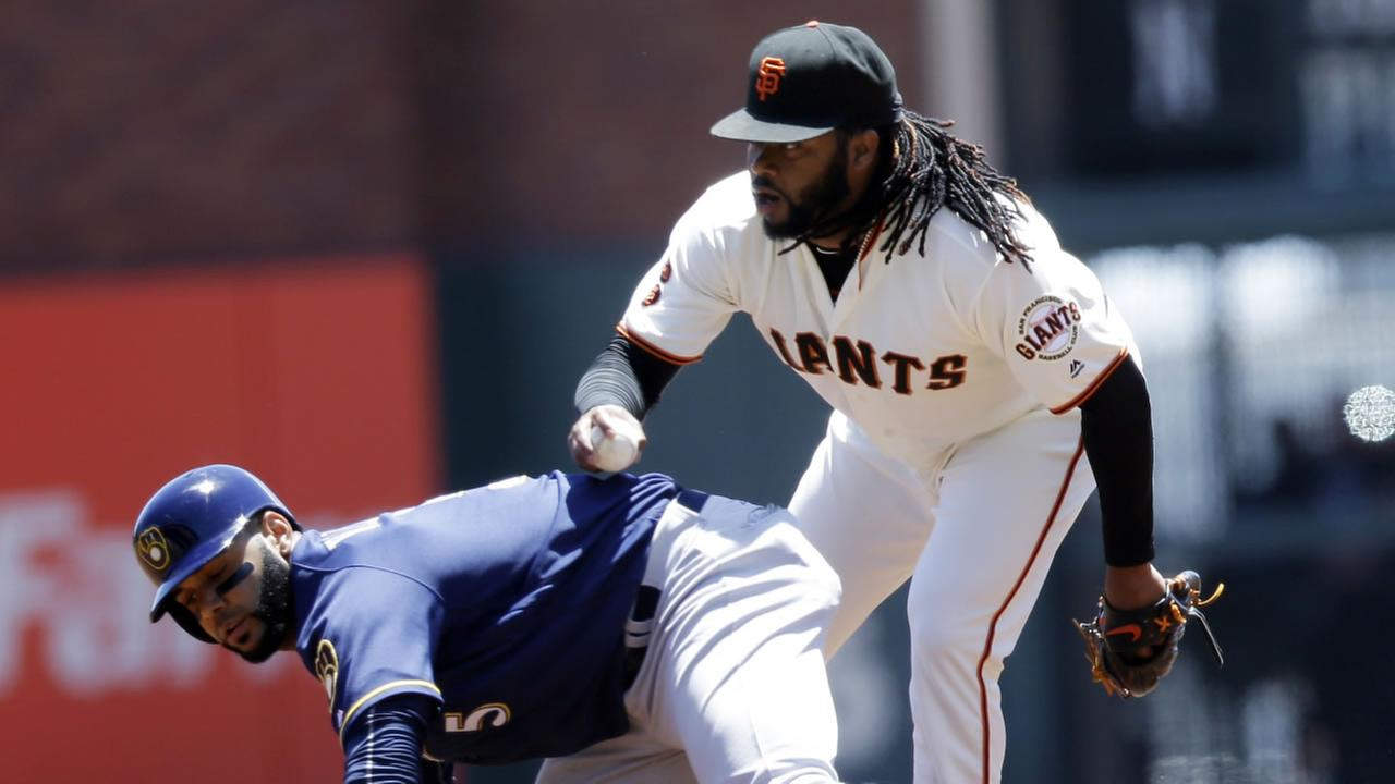 San Francisco Giants starting pitcher Johnny Cueto, right, tags out Milwaukee Brewers Jonathan Villar in a run down between first and second base June 15, 2016, in San  Francisco.