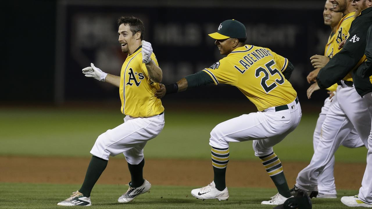 Oakland Athletics Billy Burns, left, celebrates with Tyler Ladendorf (25) after making the game winning hit against the Los Angeles Angels June 17, 2016, in Oakland, Calif.