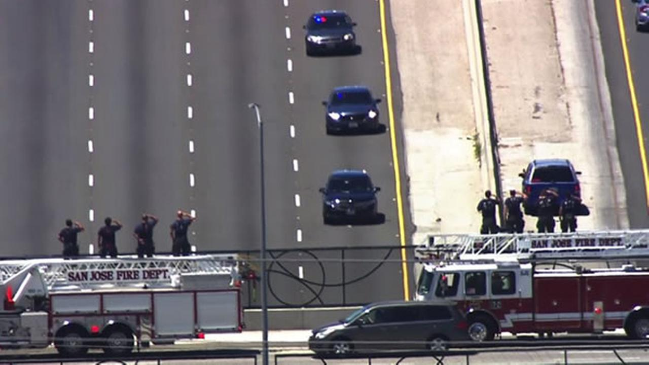 San Jose firefighters salute the procession for fallen Officer Michael Katherman as it passes on its way to Gilroy, Calif. on Tuesday, June 21, 2016.KGO-TV