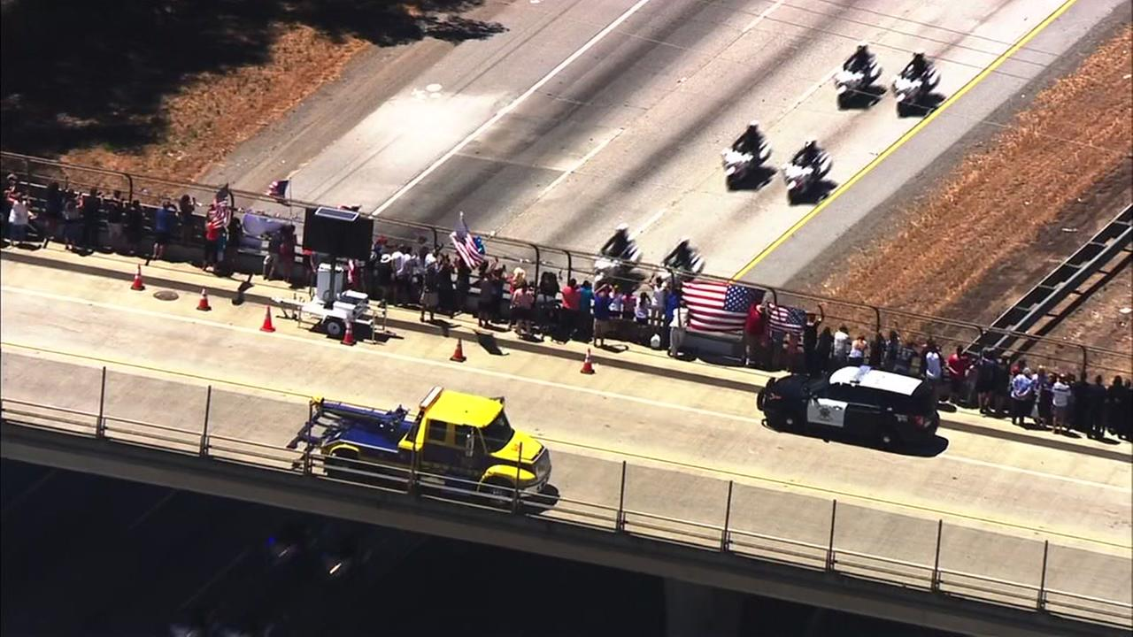 Crowds pay tribute to fallen Officer Michael Katherman as his funeral procession drives by on its way to Gilroy, Calif. on Tuesday, June 21, 2016.KGO-TV