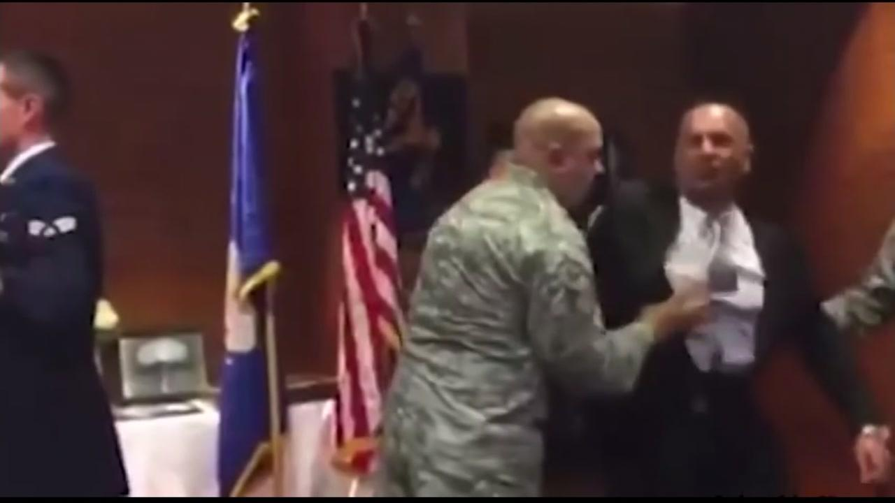 This image shows retired Air Force Master Sergeant Oscar Rodriguez physically removed from a colleagues retirement ceremony.