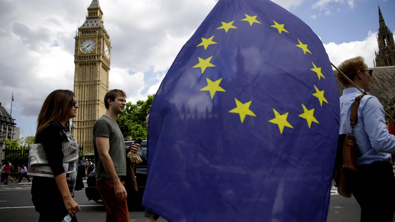A remain supporter stops to talk to people as he walks around with his European flag across the street from the Houses of Parliament in London, Friday, June 24, 2016.