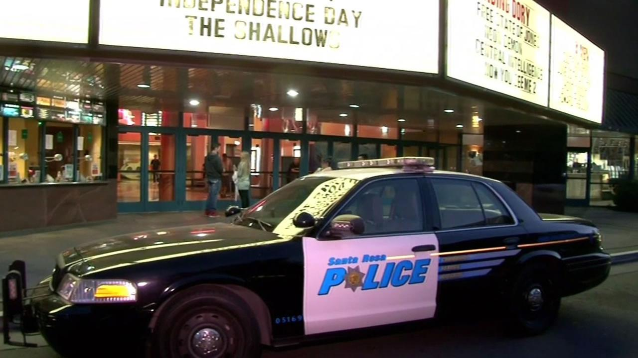This image shows a police officer investigating a stabbing at a Santa Rosa, Calif. movie theater.