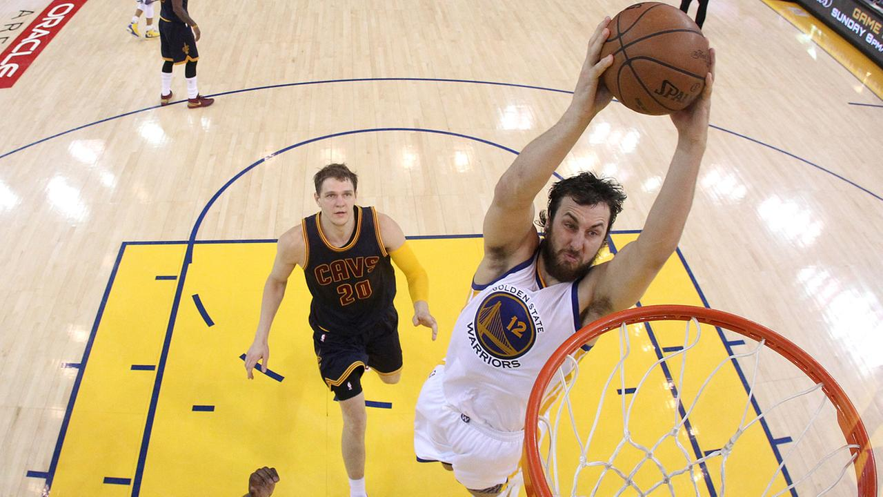 FILE -- Warriors center Andrew Bogut (12) dunks against Cavaliers center Timofey Mozgov (20) during the second half of Game 1 of basketballs NBA Finals in Oakland,  June 4. 2015.