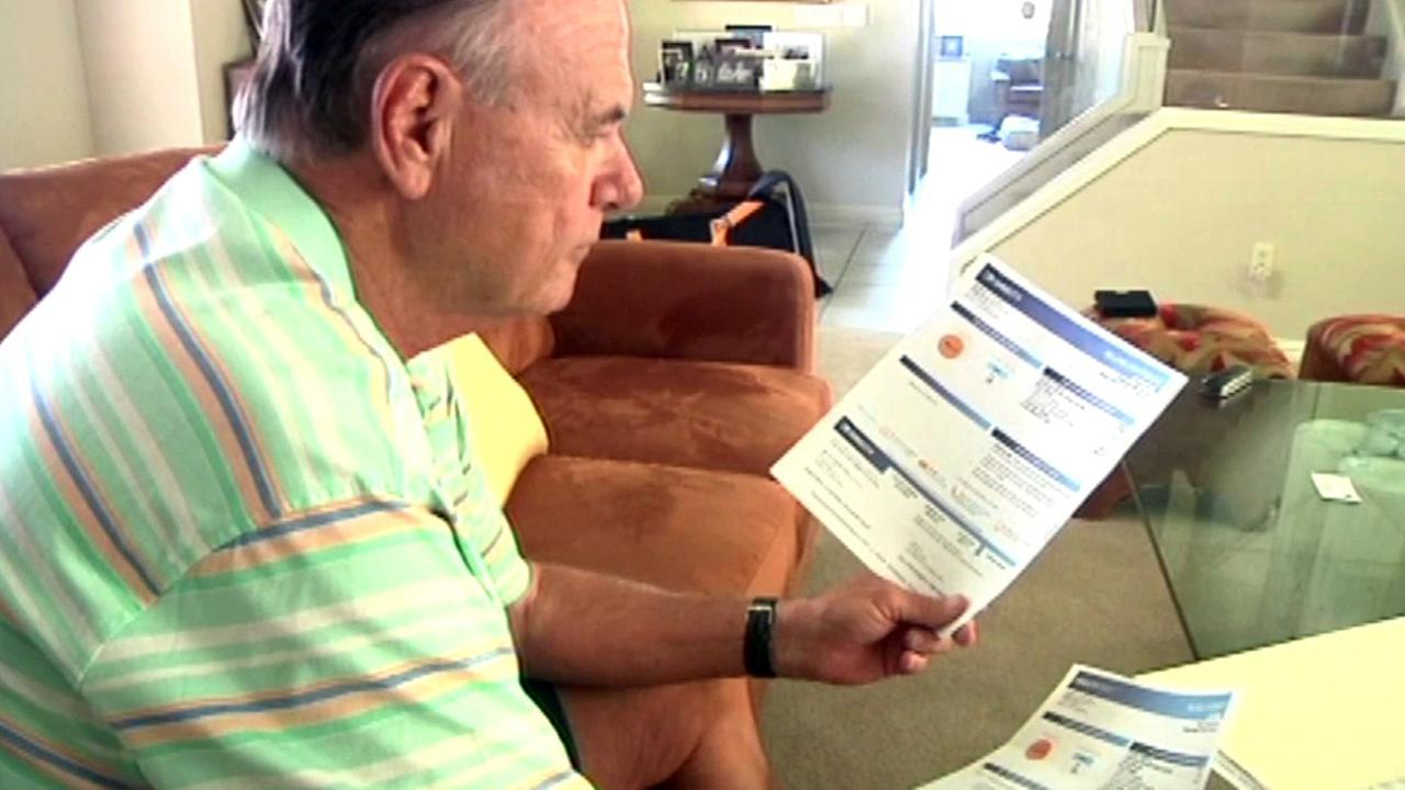 Man looks at DirecTV bill.