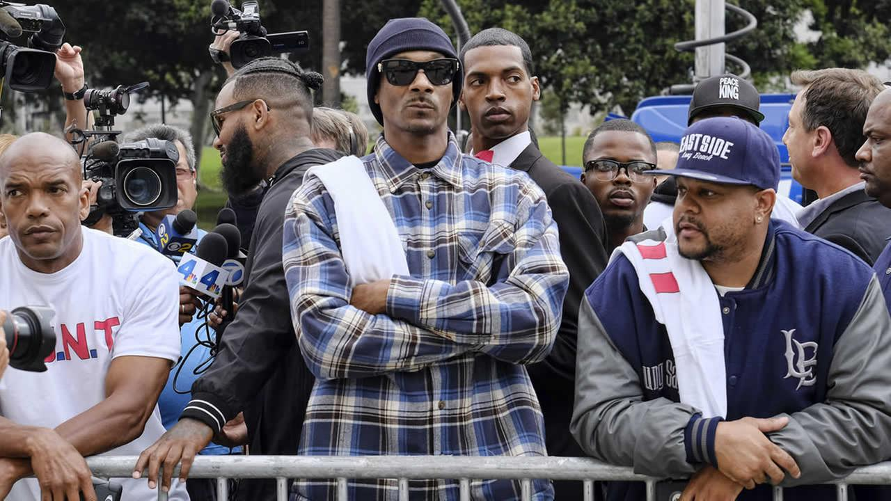 Rapper Snoop Dogg, center, leads a march in support of unification outside of the graduation ceremony for the latest class of Los Angeles Police recruits in Los Angeles, Friday, July 8, 2016. (AP Photo/Richard Vogel)