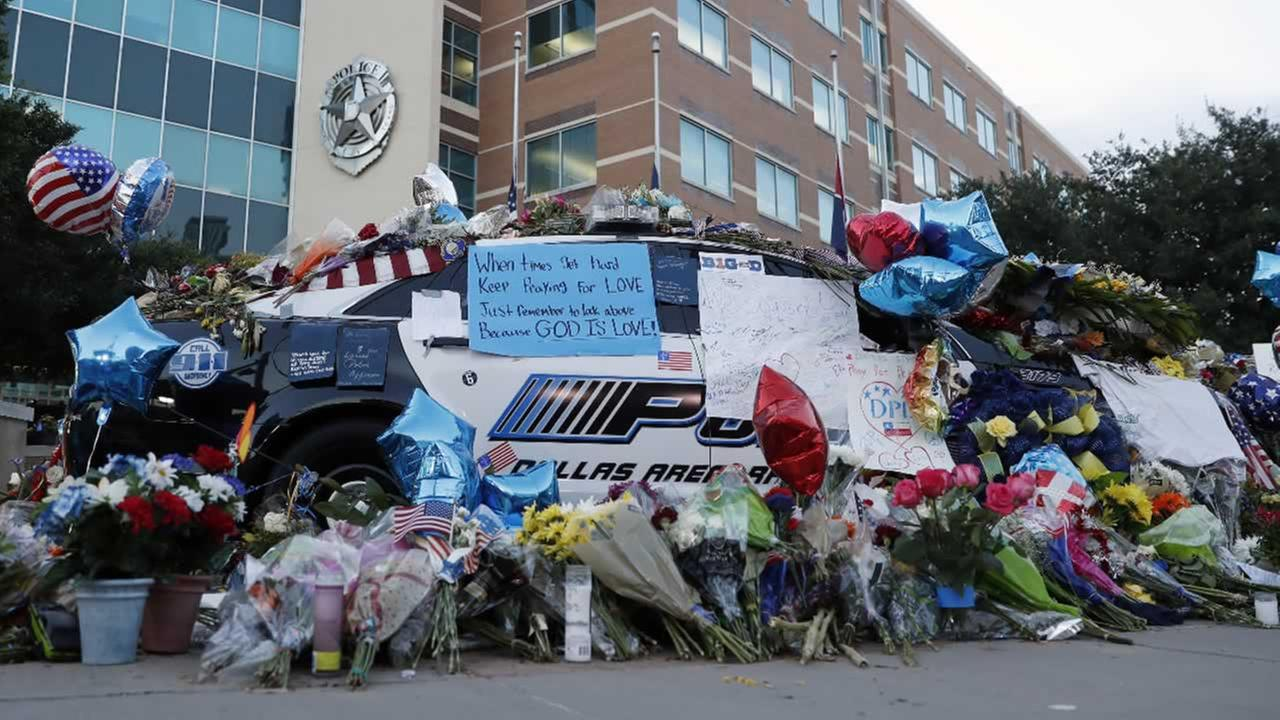 Two Dallas police patrol cars are covered with notes, flowers, balloons and other items as part of a makeshift memorial at the headquarters, Sunday, July 10, 2016, in Dallas.