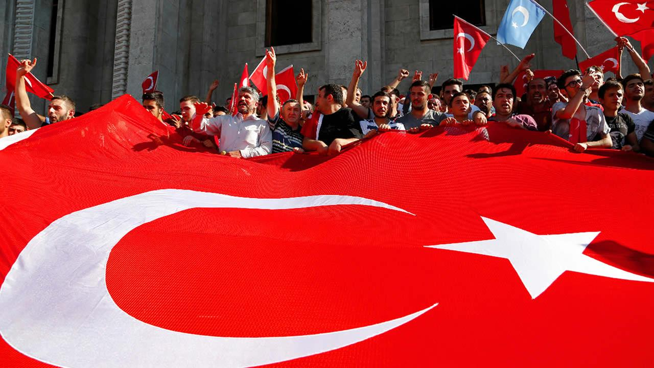 Turkish citizens wave a huge national flag as they protest against the military coup outside Turkeys parliament in Ankara, Turkey, Saturday, July 16, 2016.