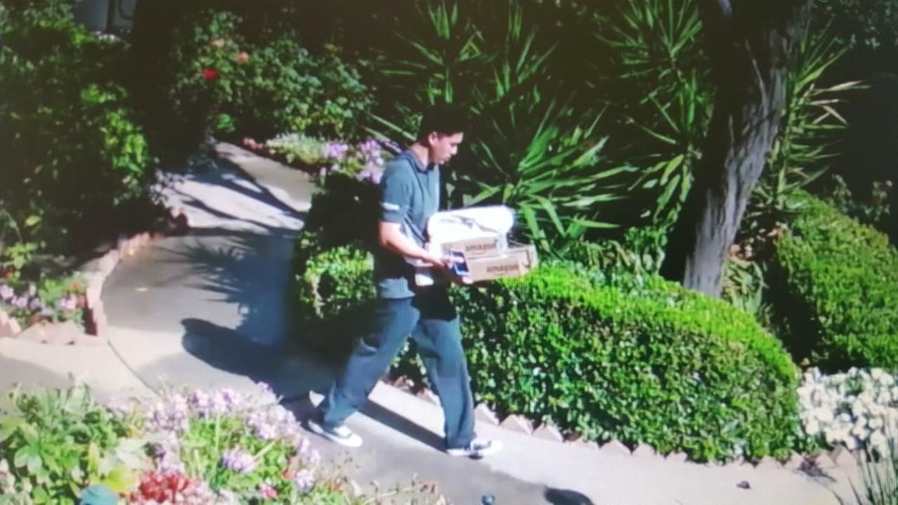 An Amazon delivery man is seen holding a package near a home in San Jose, Calif. in this undated surveillance video.
