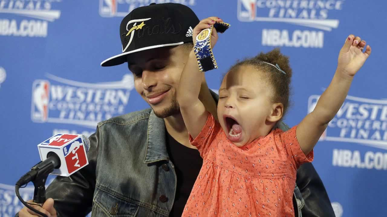 In this May 27, 2015, file photo, Golden State Warriors guard Stephen Curry is joined by his daughter Riley at a news conference.