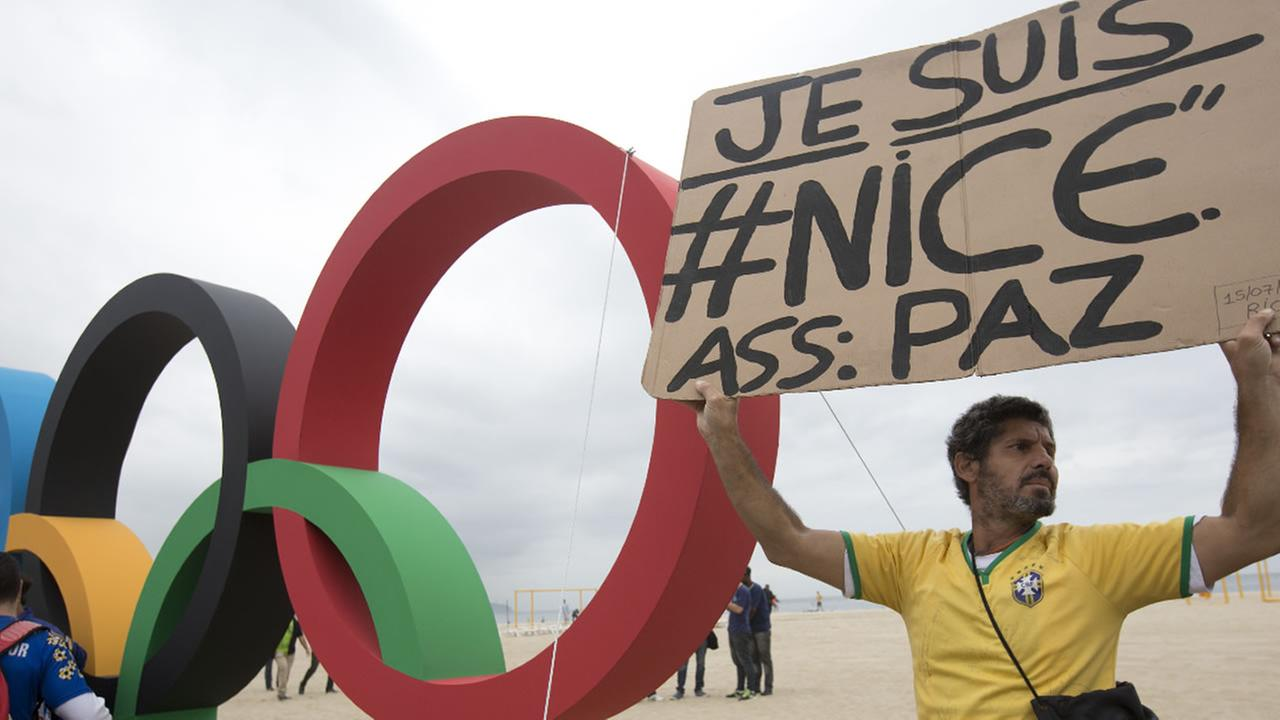 A man holds a sign to show solidarity with Nice during the presentation of Olympic rings at Copacabana beach in Rio de Janeiro, Brazil, Thursday, July 21, 2016.