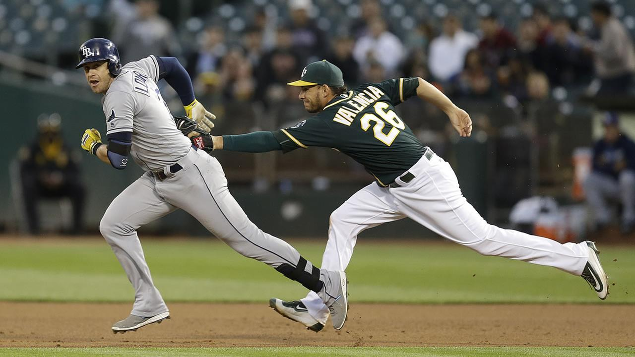 Oakland Athletics Danny Valencia, right, tags out Tampa Bay Rays Evan Longoria during a rundown between first and second base in a baseball game July 20, 2016.