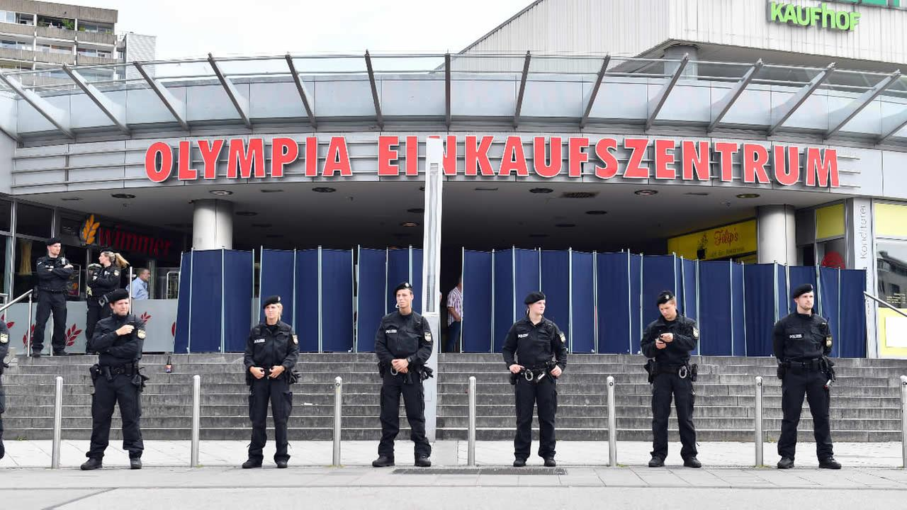 Police officers stand in front of the Olympia mall on Saturday, July 23, 2016 in Munich, Germany, one day after an 18-year-old gunman opened fire at the crowded Munich shopping mall and fast-food restaurant and killed nine people before killing himself.
