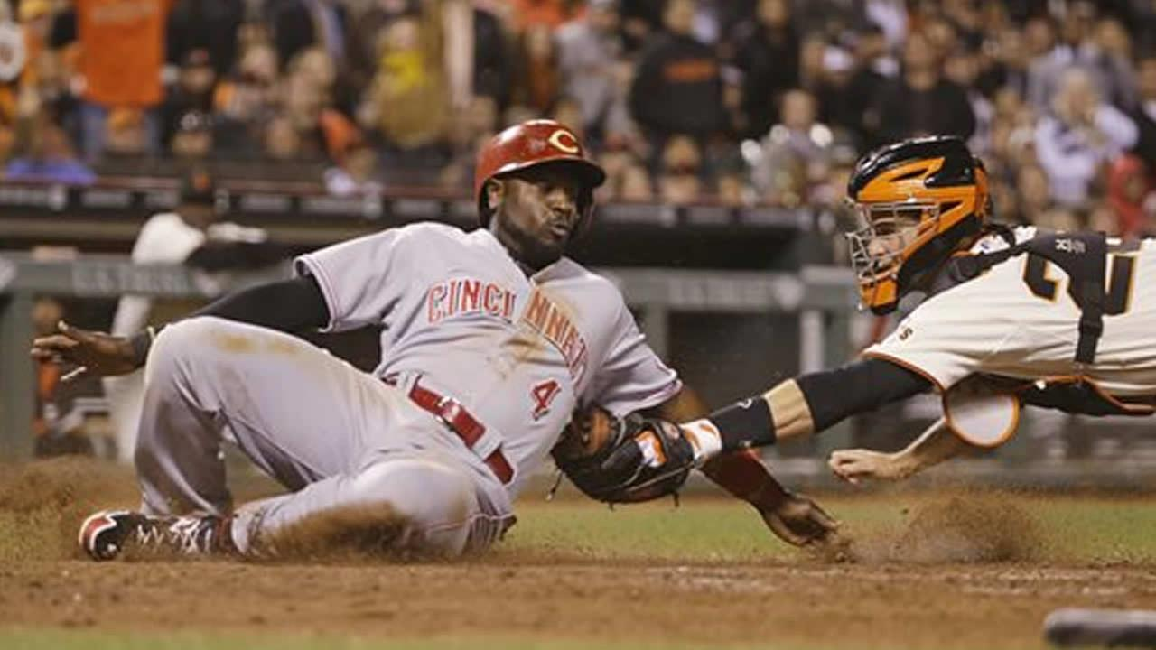Cincinnati Reds Brandon Phillips tagged out at home plate by San Francisco Giants catcher Buster Posey