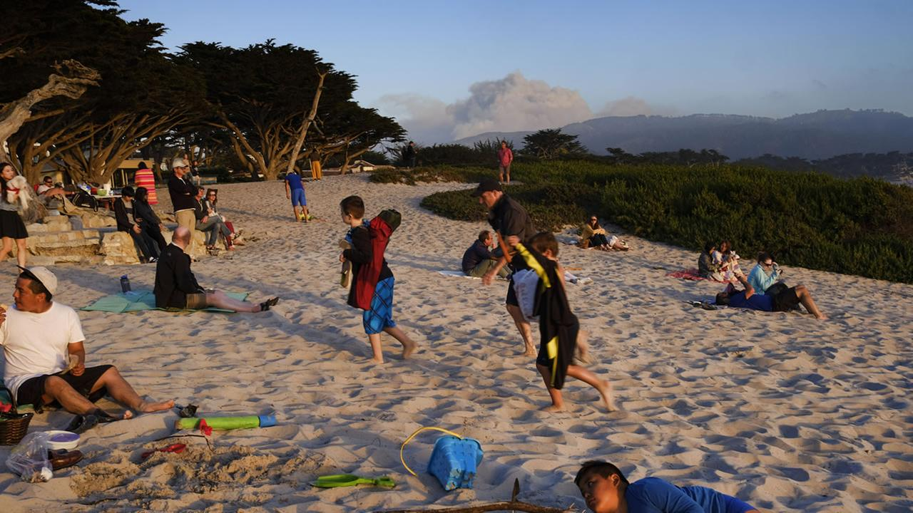 This Saturday, July 23, 2016 photo shows a large plume of smoke rising over a hilltop in the distance as people enjoy a sunset on the beach in Carmel, Calif.