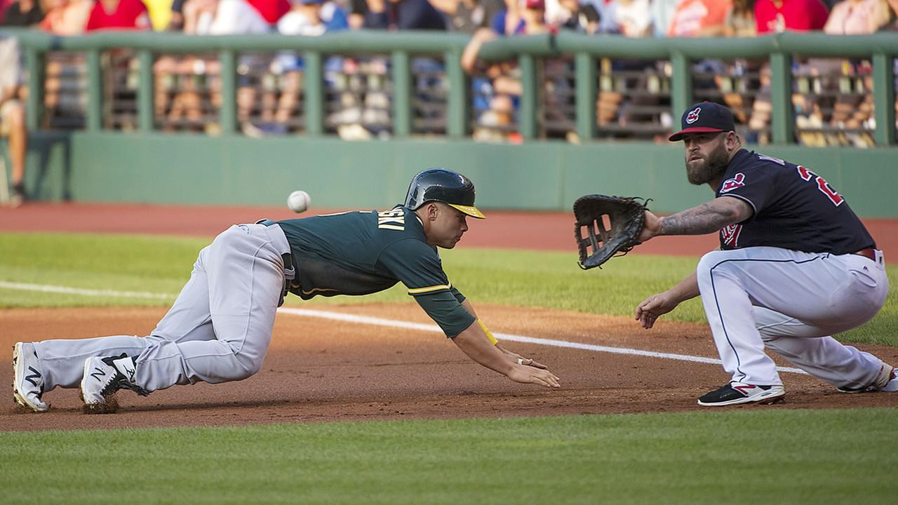 Oakland Athletics Jake Smolinski dives safely back to first base as Cleveland Indians Mike Napoli waits for the throw during the first inning of a baseball game in Cleveland.
