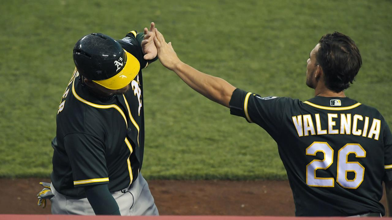 Oakland Athletics Billy Butler, left, is congratulated by Danny Valencia after scoring during a baseball game against the Los Angeles Angels, Thursday August, 4, 2016.