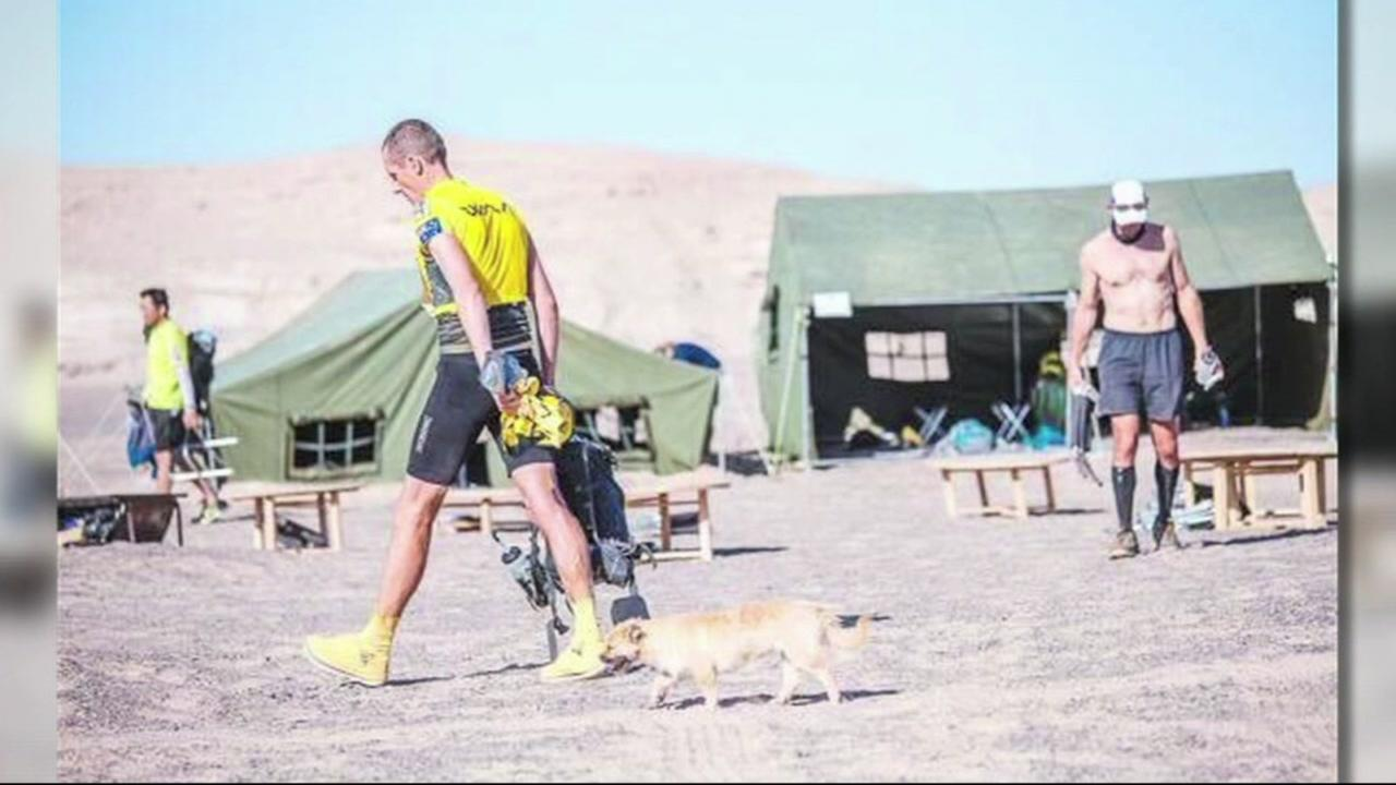 This image shows extreme marathon runner Dion Leonard with the dog he nicknamed Gobi after he tagged along for 77 miles of his trek.