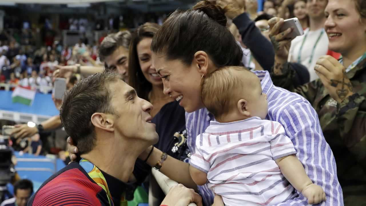 Michael Phelps celebrates winning his gold medal in the mens 200-meter butterfly with his fiance Nicole Johnson and baby Boomer, Tuesday, Aug. 9, 2016, in Rio de Janeiro, Brazil.