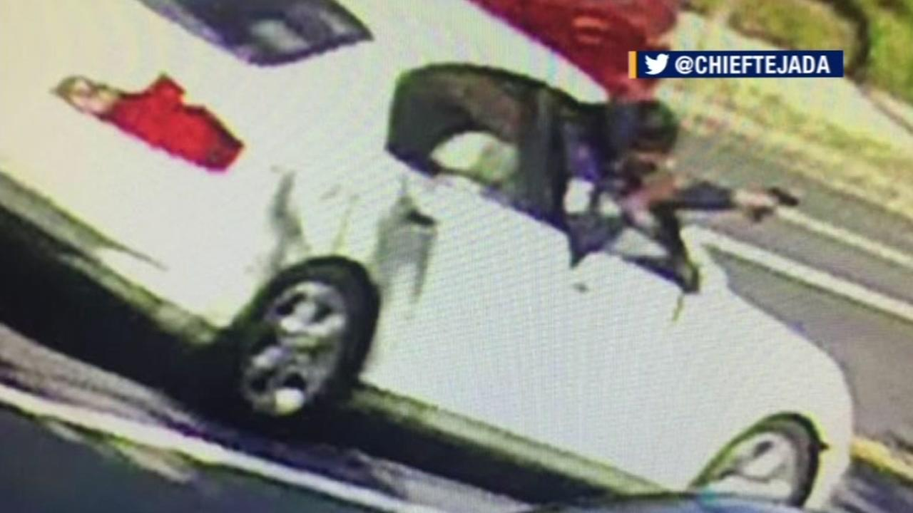This surveillance video image shows a shooter leaning out the passenger side window of a white car while firing a handgun in Emeryville, Calif. on Wednesday, August 17, 2016.