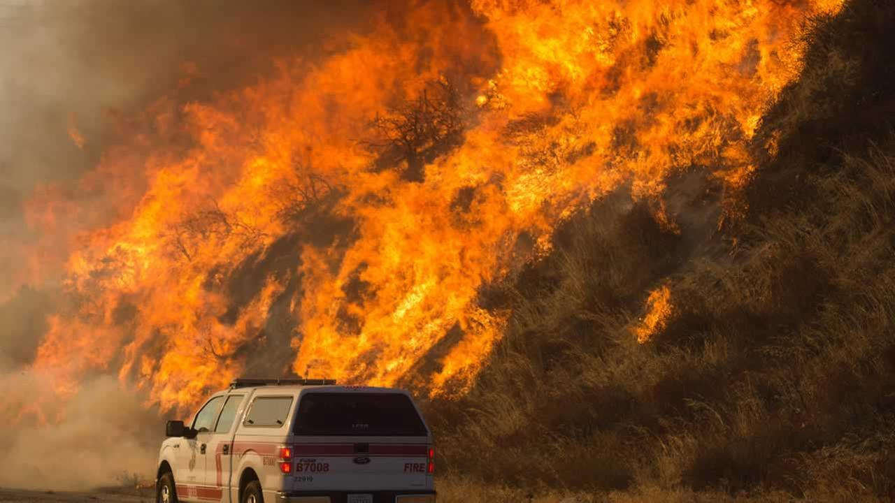 Flames from a wildfire rise above a Cal Fire vehicle in Keenbrook, Calif., on Wednesday, Aug. 17, 2016.