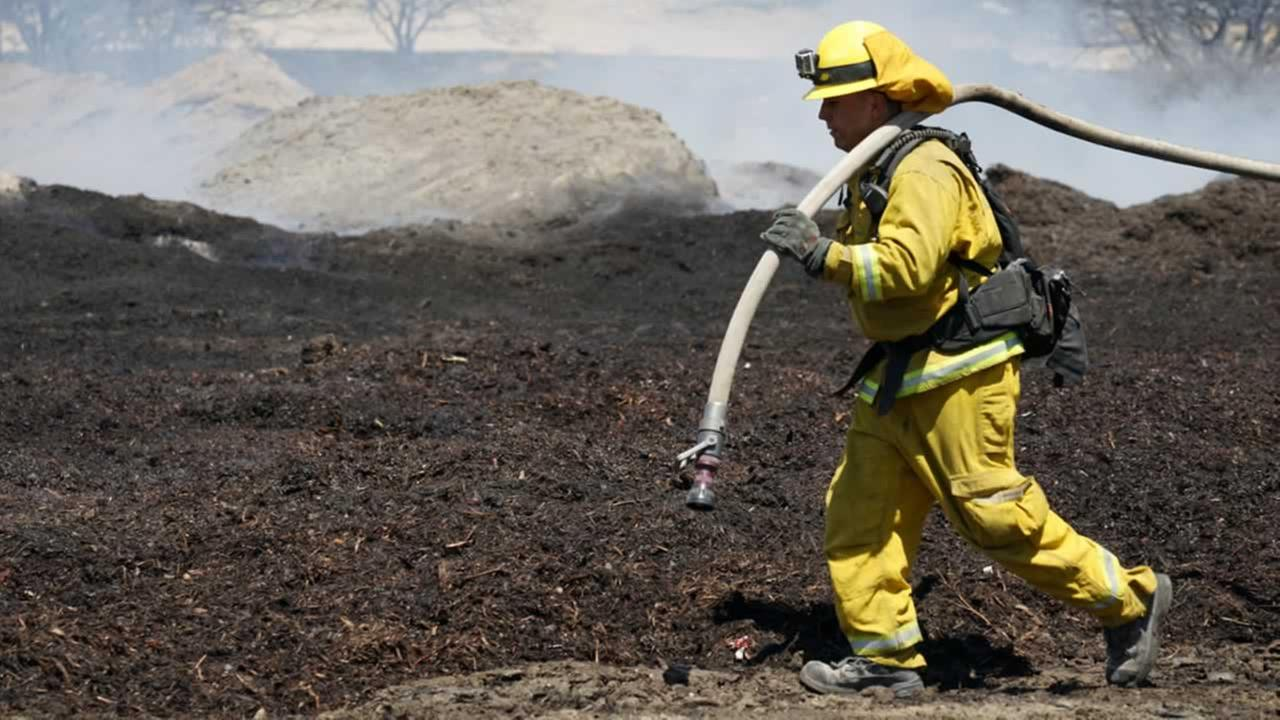 Firefighters water down scorched compost material at a property burned near Phelan, Calif., on Friday, Aug. 19, 2016.