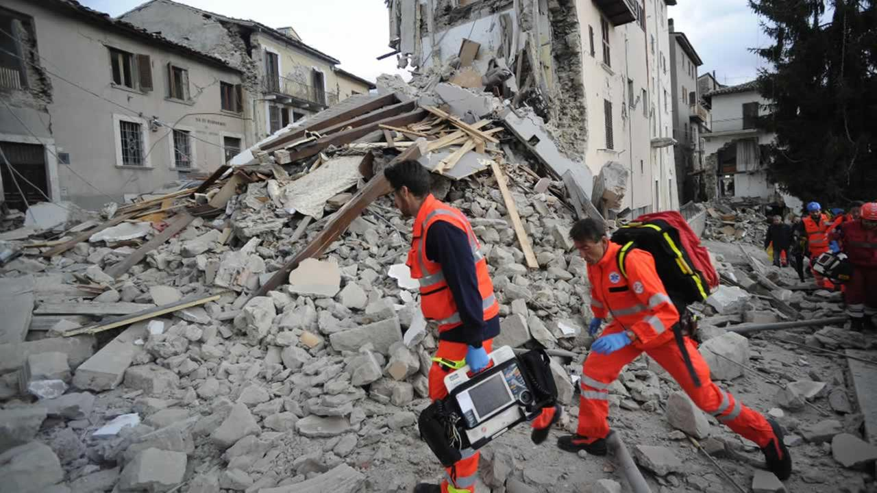 Rescuers search a crumbled building in Arcuata del Tronto, central Italy, where a 6.1 earthquake struck just after 3:30 a.m., Wednesday, Aug. 24, 2016.