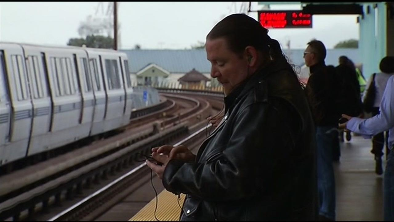 A BART rider uses their cellphone on the platform.