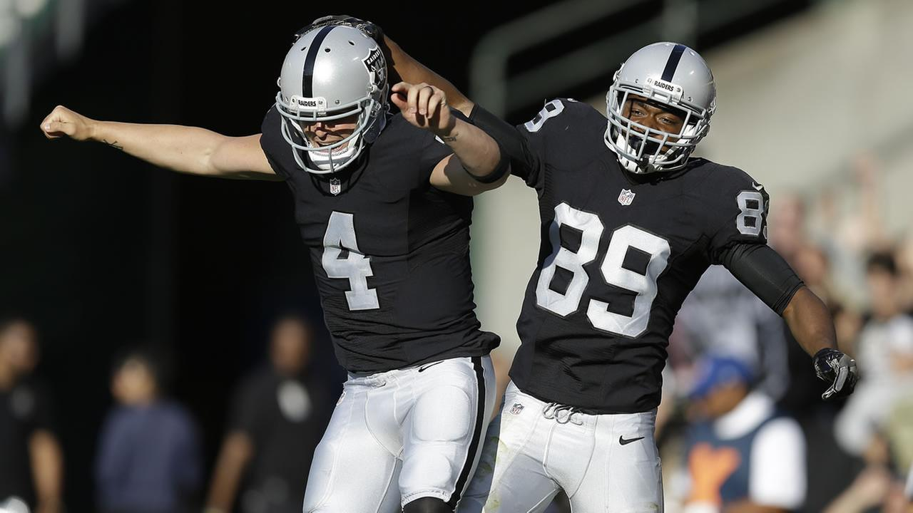 Oakland Raiders wide receiver Amari Cooper, right, celebrates with quarterback Derek Carr, left, after scoring a touchdown during a preseason football Aug. 27, 2016, in Oakland.