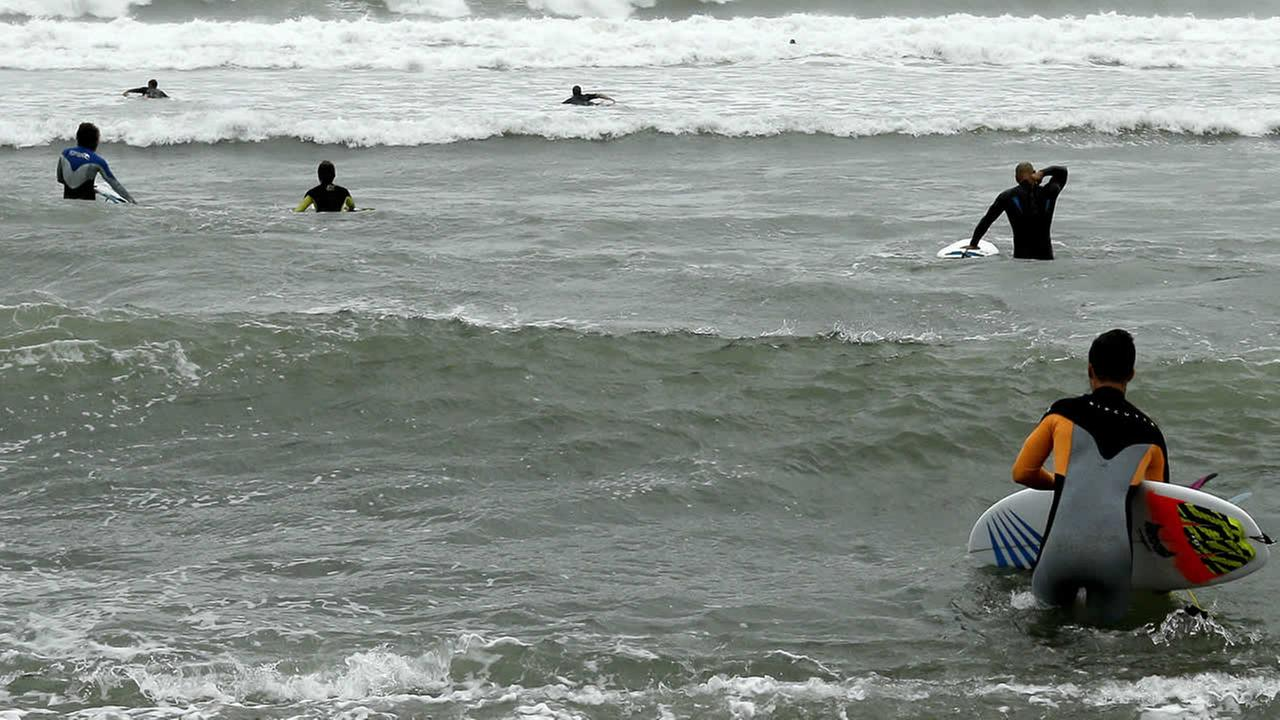Surfers make their way toward waves Tuesday, Sept. 6, 2016, along the coast of South Kingstown, R.I., as  Tropical Storm Hermine begins to weaken.