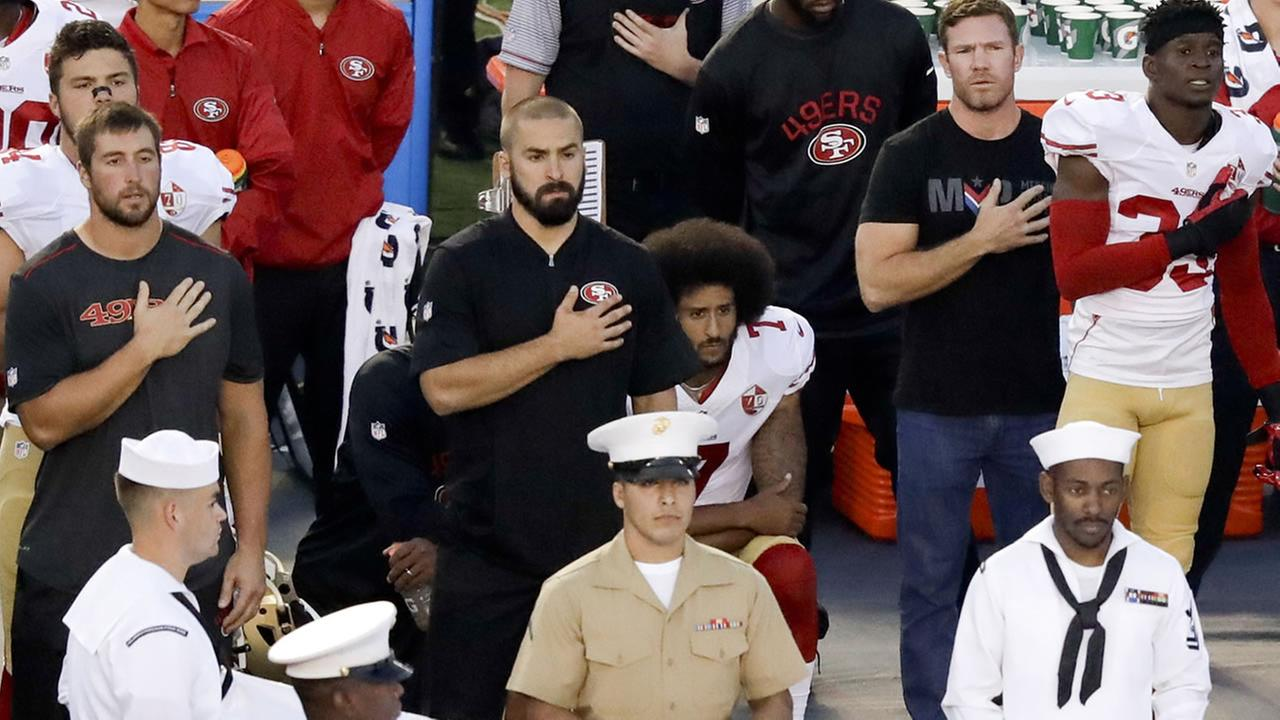 In this Sept. 1, 2016 file photo, 49ers QB Colin Kaepernick, center, kneels during the national anthem before an NFL preseason football game against the Chargers in San Diego.