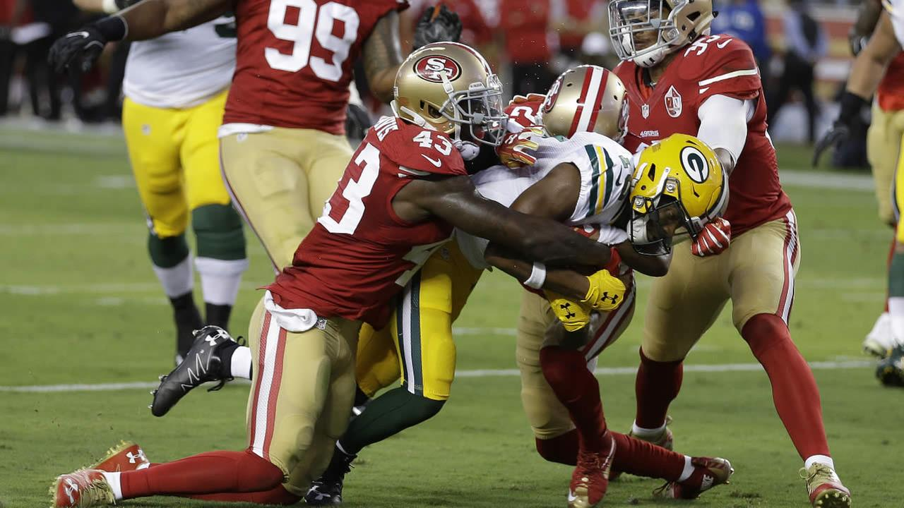 49ers cornerback Chris Davis (43) and free safety Eric Reid, right, try to stop Packers receiver Randall Cobb in a preseason  game Friday, Aug. 26, 2016, in Santa Clara, Calif.