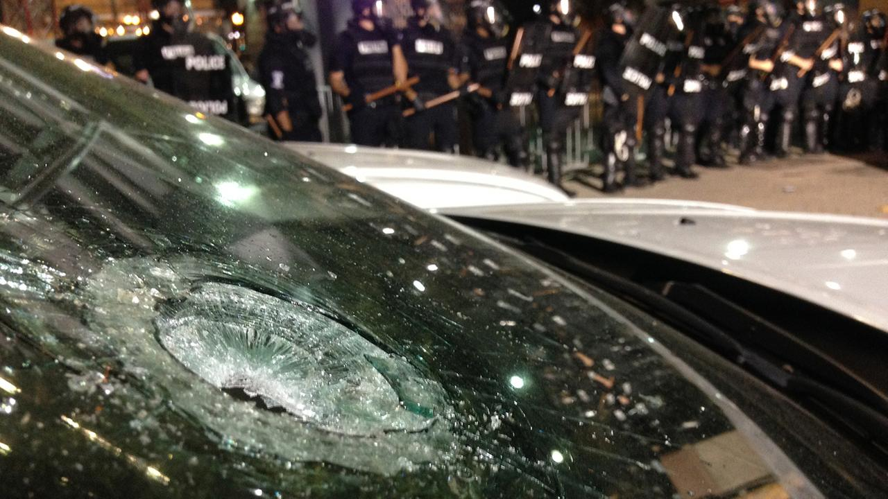 A police vehicle is damaged as police fire teargas as protestors converge on downtown following police shooting of Keith Lamont Scott in Charlotte, N.C., Wednesday, Sept. 22, 2016.