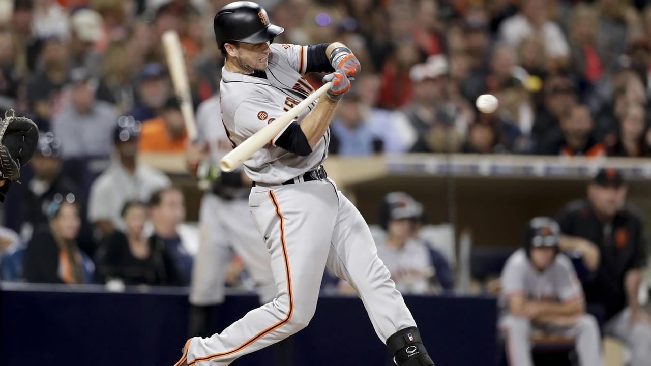 San Francisco Giants Buster Posey hits a two-RBI double during the fifth inning of a baseball game against the San Diego Padres Friday, Sept. 23, 2016, in San Diego.