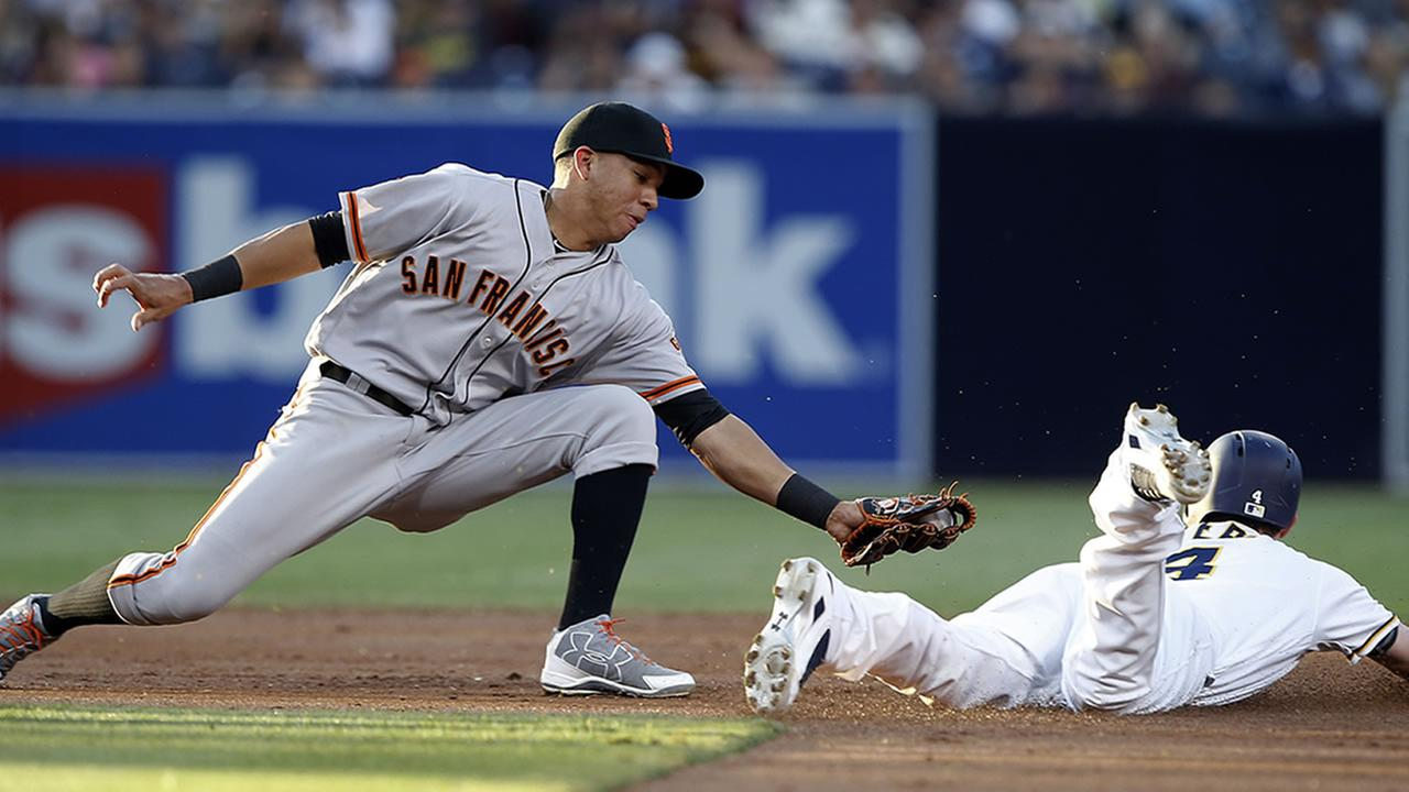 San Diego Padres Wil Myers, right, steals second base as San Francisco Giants shortstop Ehire Adrianzas tag is late during the first inning of a baseball game in Sept. 24, 2016.