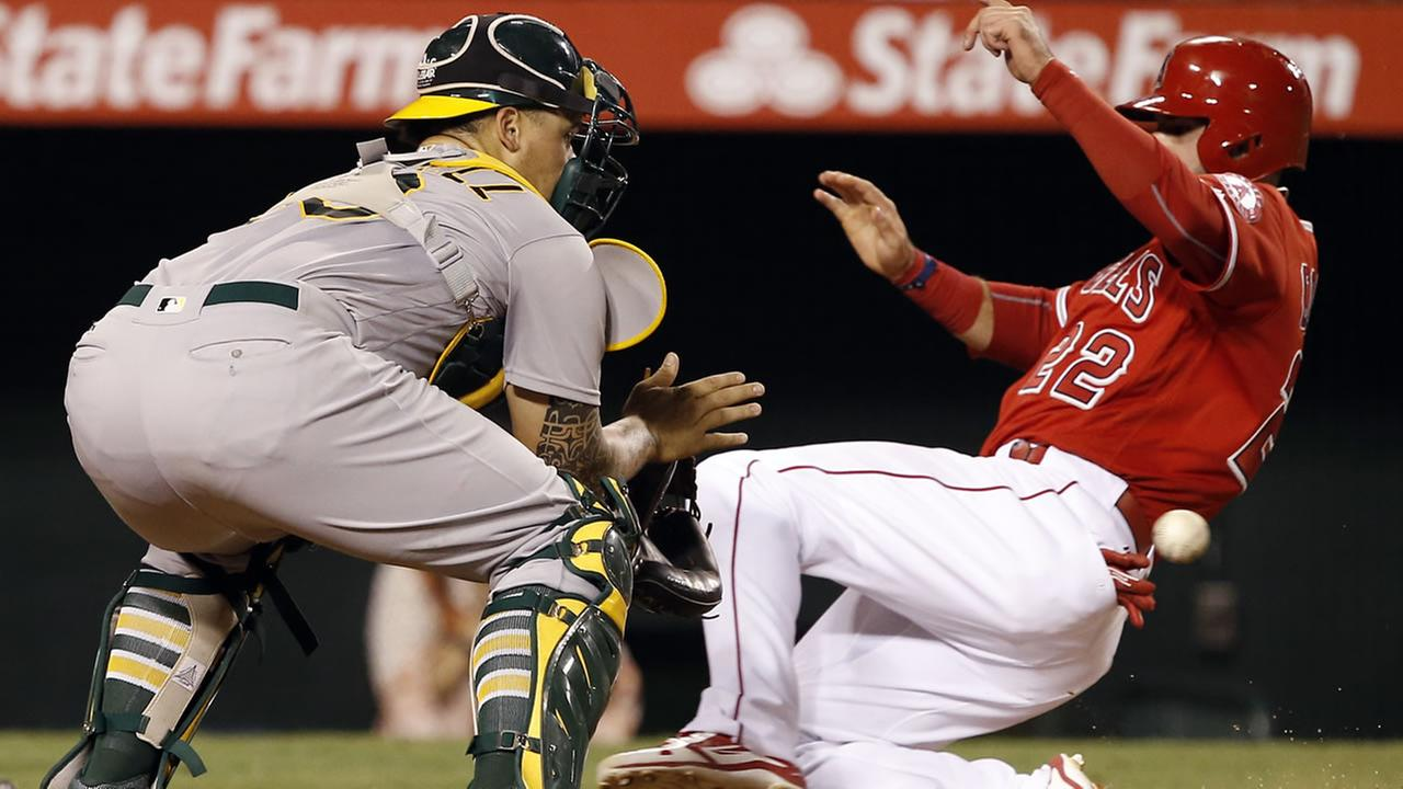 Athletics Bruce Maxwell waits for the throw as Angels Kaleb Cowart slides in safely on a double by Shane Robinson during a game in Anaheim, Calif., Sept. 28, 2016. (AP Photo)