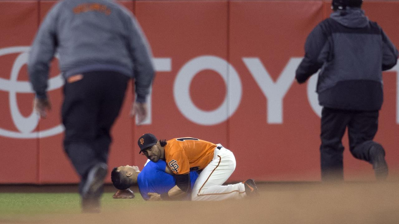 San Francisco Giants Angel Pagan (16) holds down a man who ran onto the field during the Giants baseball game against the Los Angeles Dodgers, Sept. 30, 2016 in San Francisco.