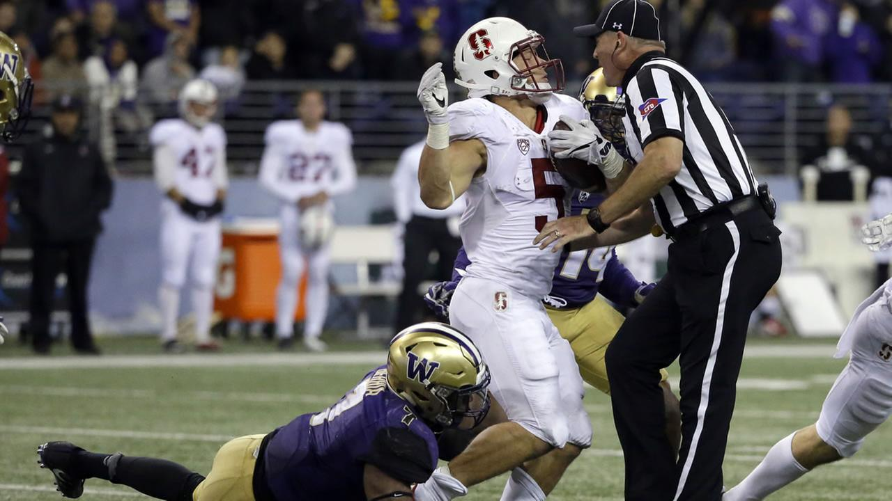 Umpire Tim Schroeder starts to go down after colliding with Stanford running back Christian McCaffrey, center, in an NCAA college football game between Washington  Sept. 30, 2016.
