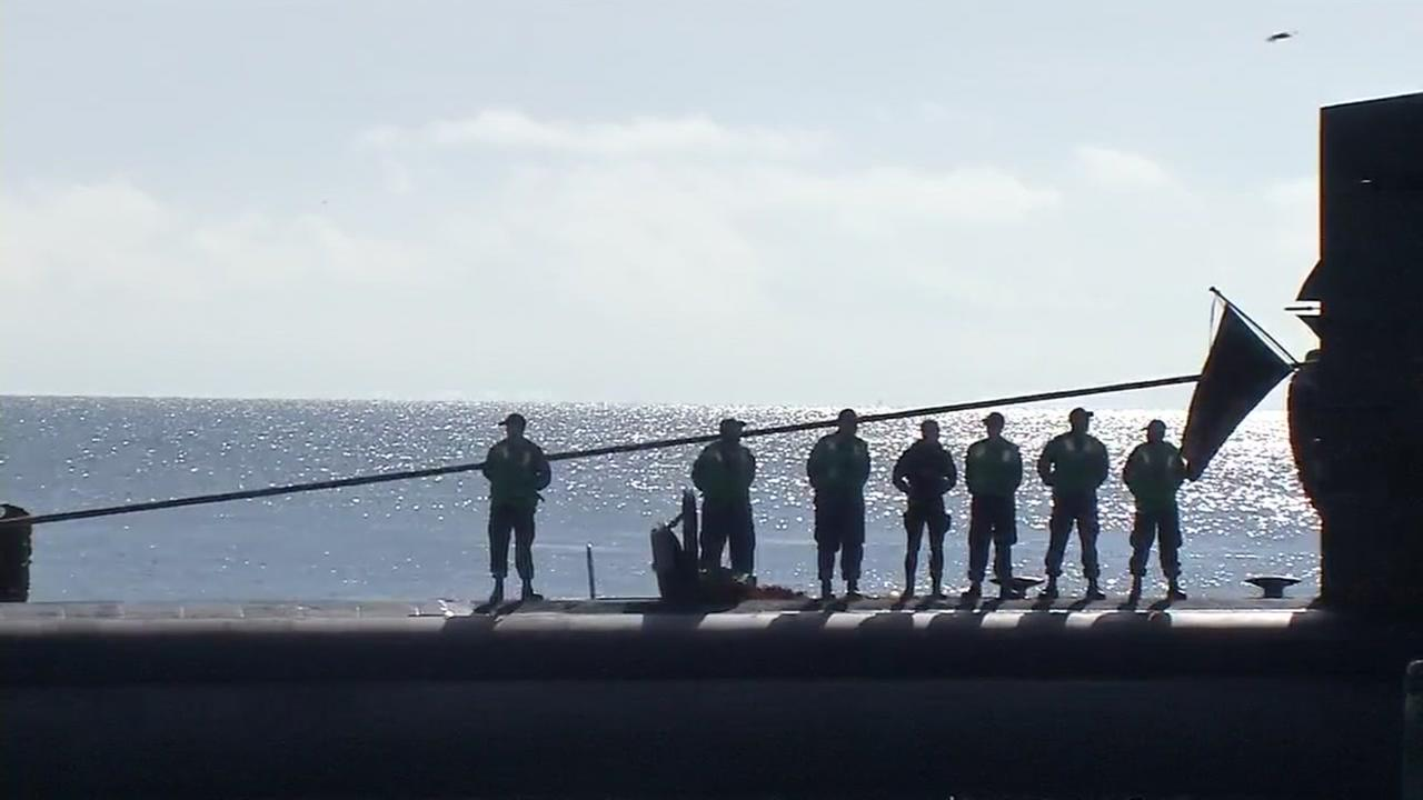 Men are pictured on top of the USS San Francisco as they work to secure it in San Francisco Bays Pier 80 on Oct. 10, 2016.