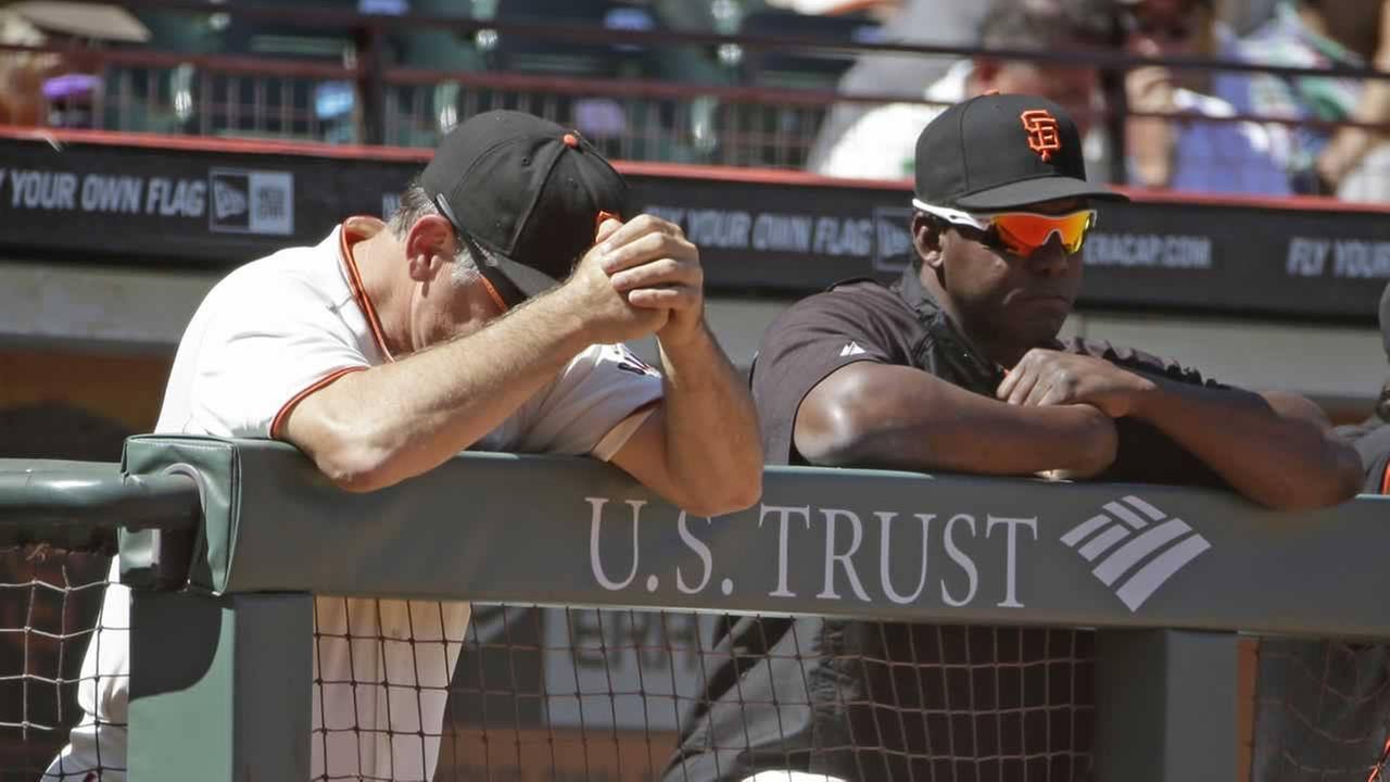 San Francisco Giants manager Bruce Bochy and hitting coach Hensley Meulens, right, rest on the dugout railing in the ninth inning of their baseball game against the Cardinals.