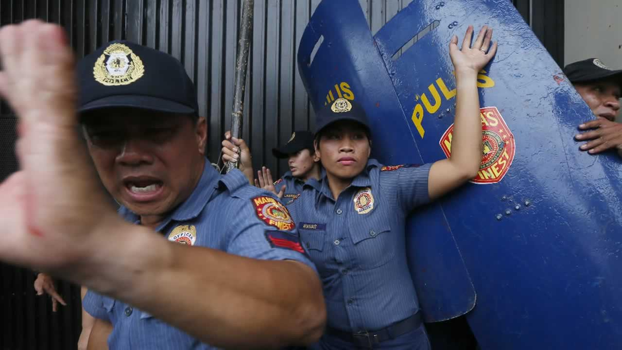 Riot police react as protesters force their way closer to the gates of the U.S. Embassy during a violent dispersal in Manila, Philippines Wednesday, Oct. 19, 2016.