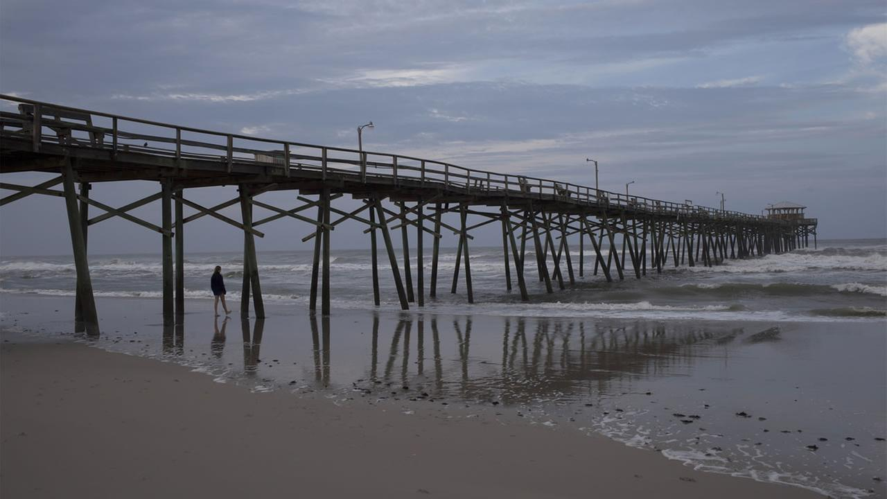 A beachcomber walks by the Oceanana Fishing Pier in Atlantic Beach, N.C., Friday, July 04, 2014.
