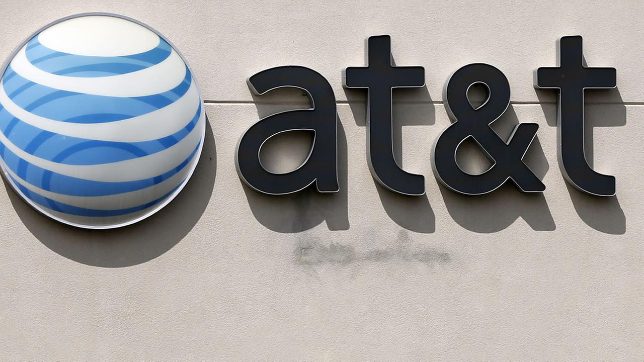 This May 14, 2014 file photo shows an AT&T logo on a store in Dedham, Mass.