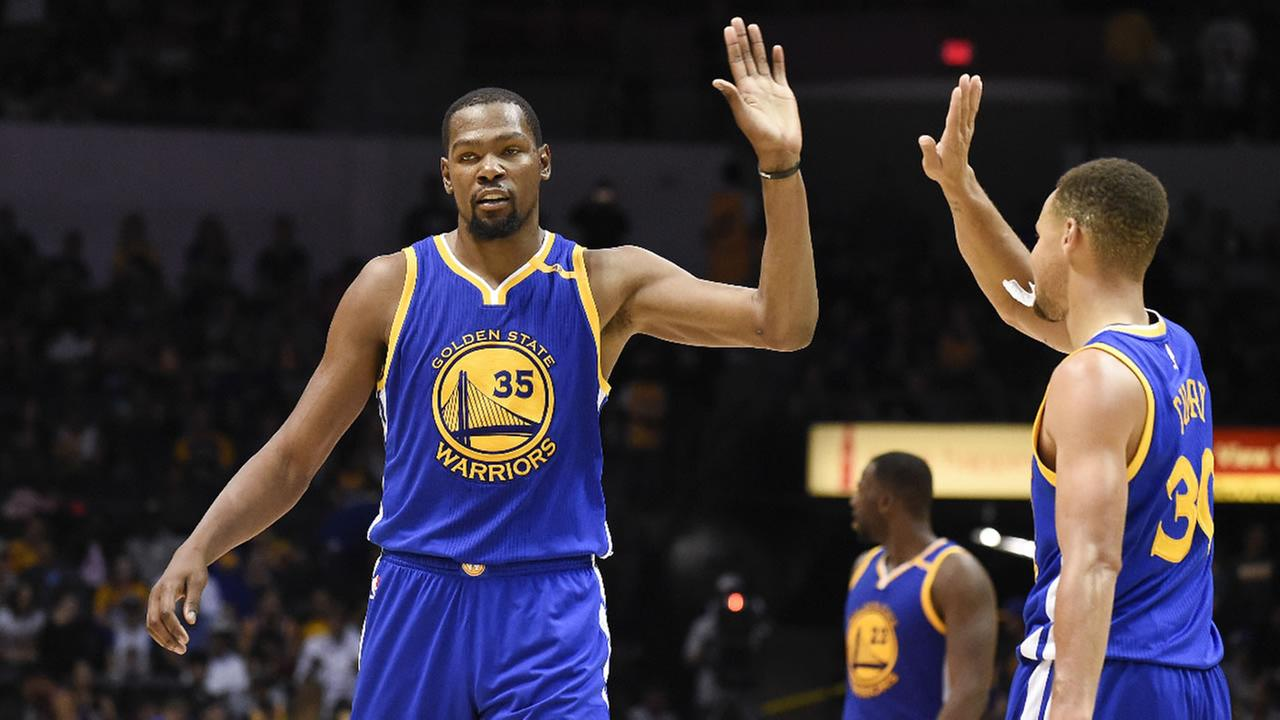 Golden State Warriors forward Kevin Durant, left, high-fives Stephen Curry on Wednesday, Oct. 19, 2016, in San Diego.