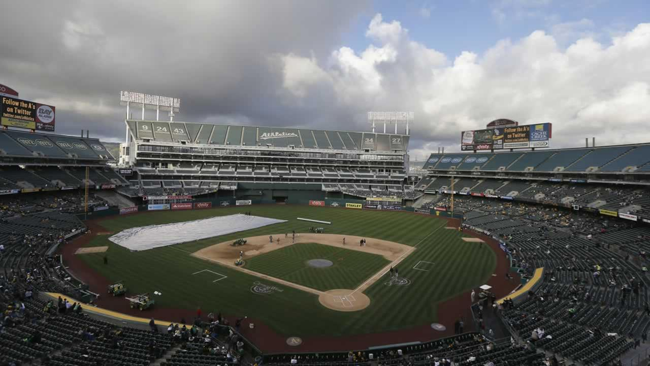 Members of the grounds crew work on the infield at O.co Coliseum before a baseball game.